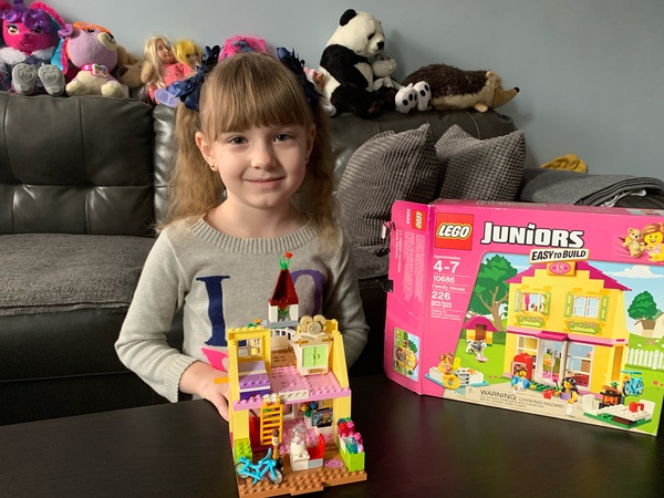 Girl happily shares her house she made with legos