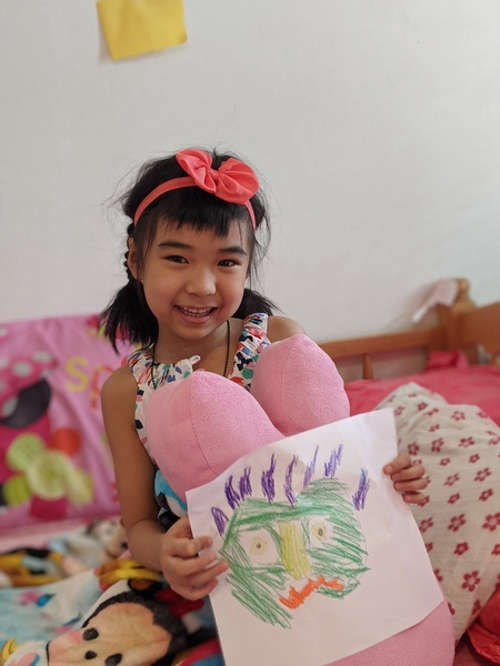girl with a pink bow in her hair holds up her drawing