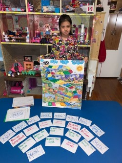 child holds up the game with the pieces on the table