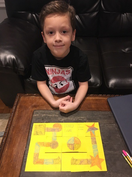 child in a black shirt sits behind the yellow paper