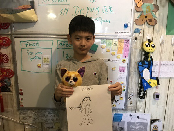boy holds stuffed cat and his work