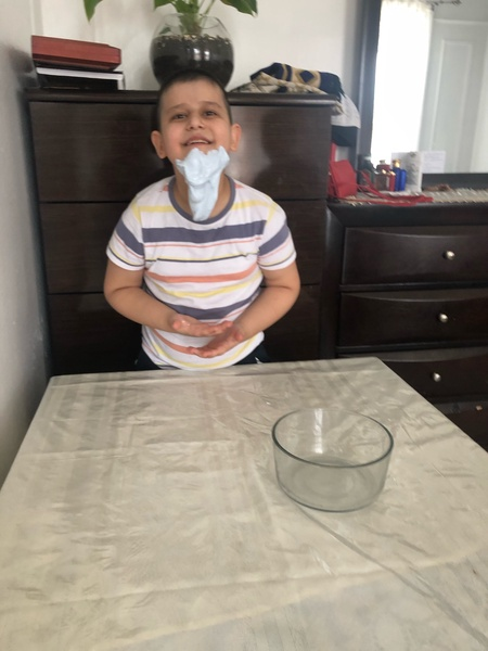 child has his project hanging from his mouth