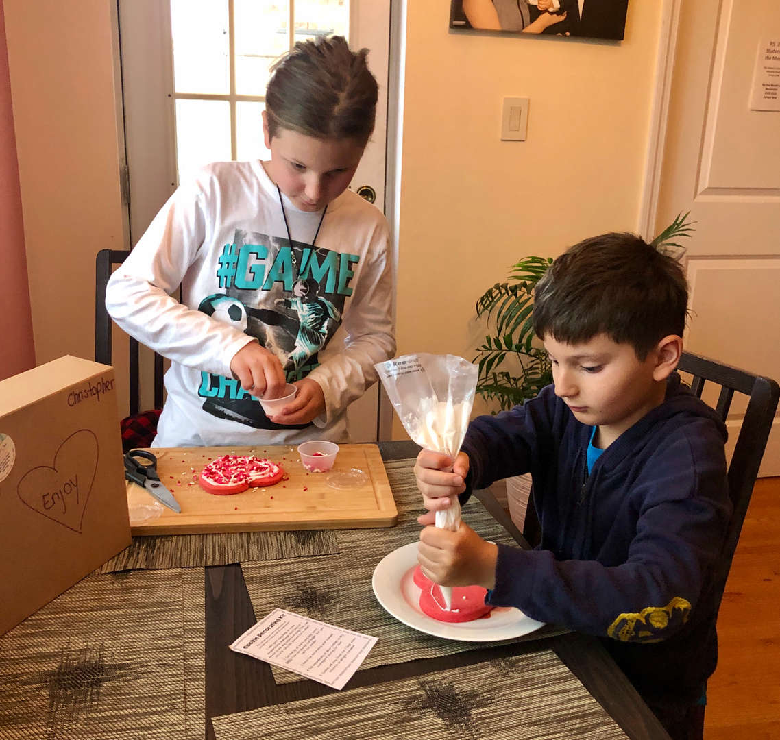 boys using icing to decorate their heart cookies