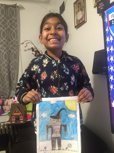 Girl with big smile shows her art work