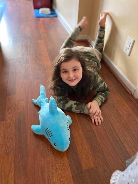 the child poses on the floor near the stuffed shark