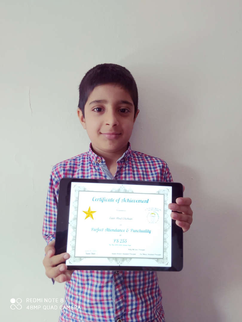 boy dressed in a button down shirt holds up his certificate