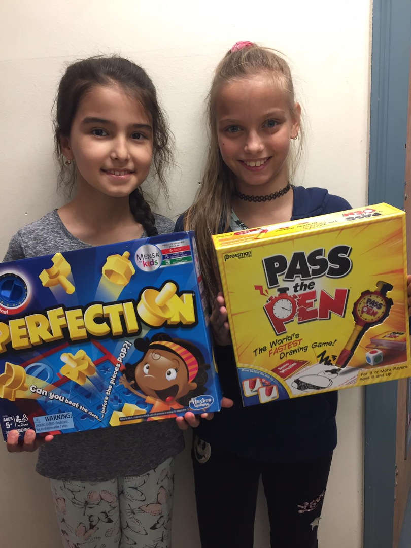 Two girls hold the games they won.