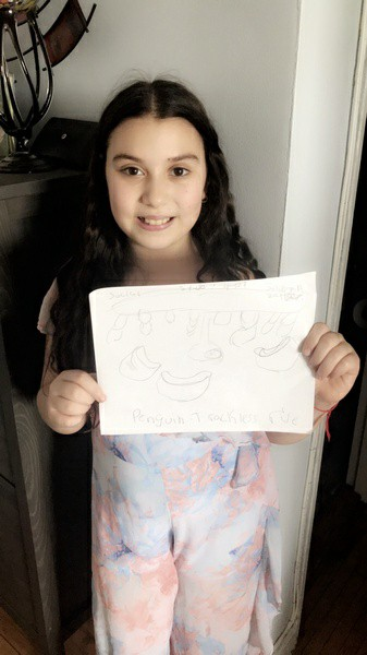 girl smiles as she shows her sea world writing