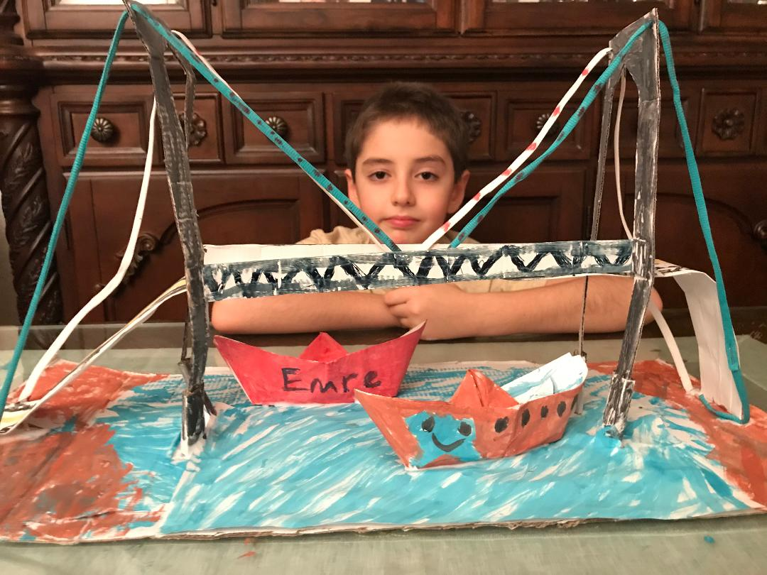 large bridge with boats below and the child who made them