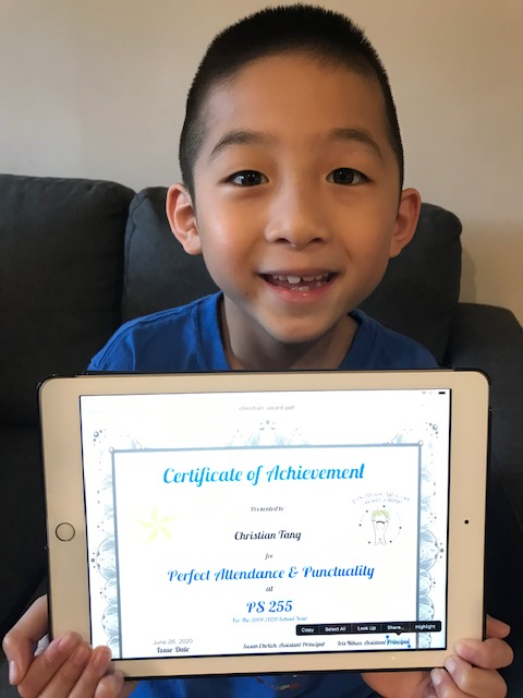 smiling boy holds his certificate while seated on a black couch