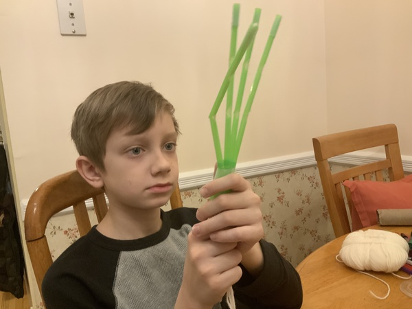 the child looks at the green strips of paper