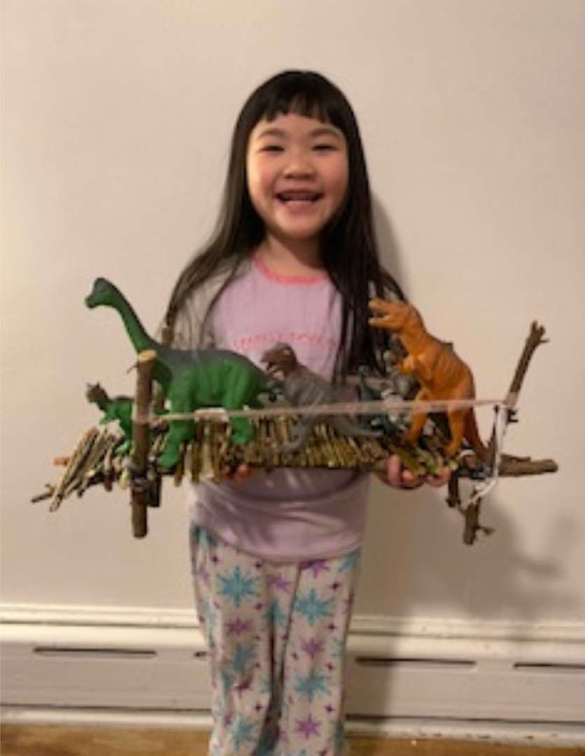 girls holds the bridge she made with dinosaurs