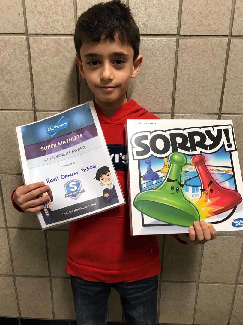 Student holds Sorry game and a certificate.