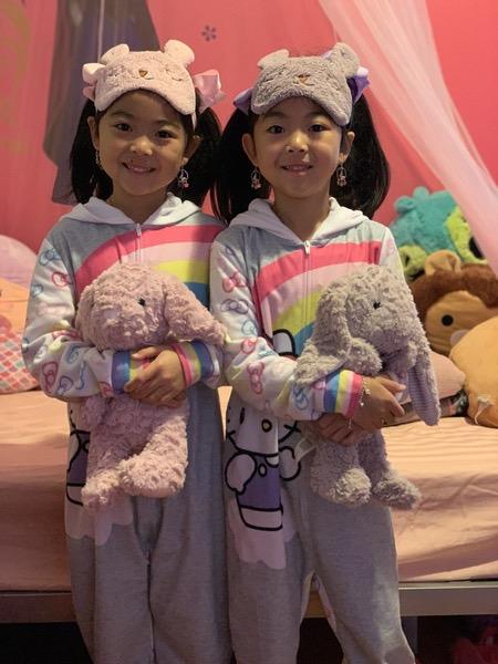 twins in their pajamas hold stuffed bunnies