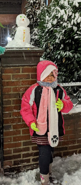 a girl dressed warmly with her snowman