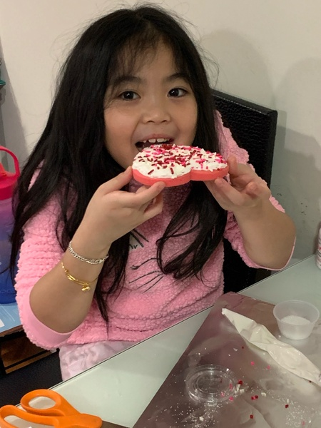 student in pink shirt about to bite her decorated cookie