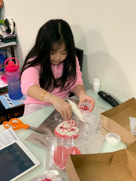 student in pink shirt adding sprinkles to her cookie