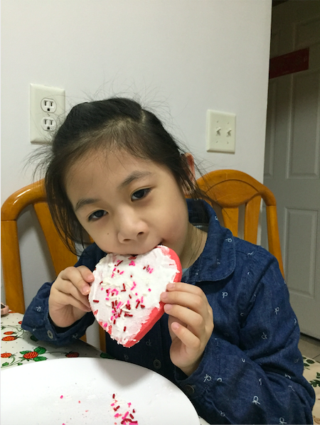child taking a bite of the heart shaped cookie