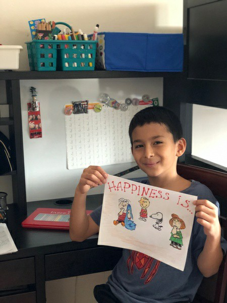boy smiles with his work