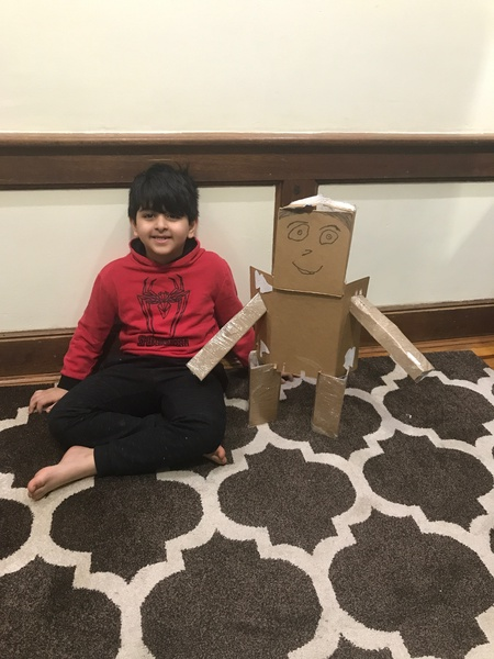a robot made of cardboard next to the boy