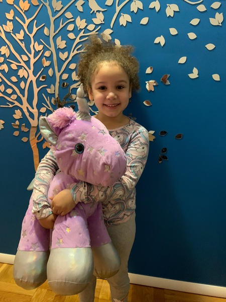 child stands in pajamas holding a large pink unicorn