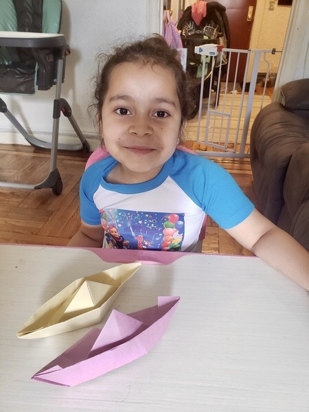 child sits at the table with the boats she made