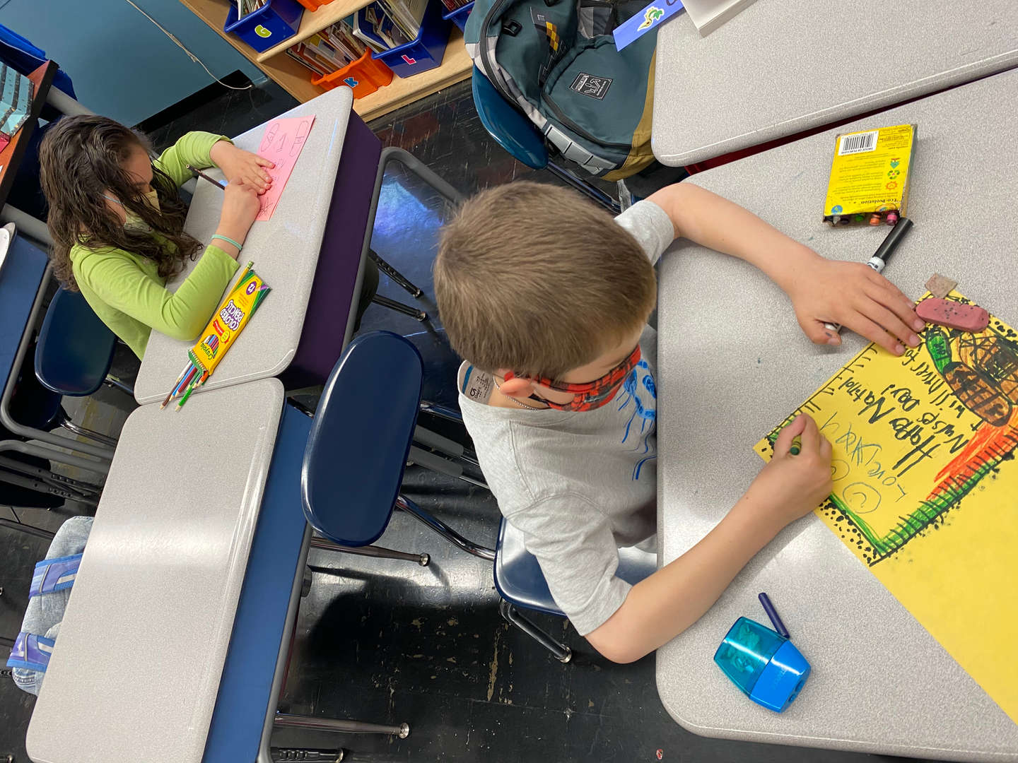 a student drawing a yellow thank you card