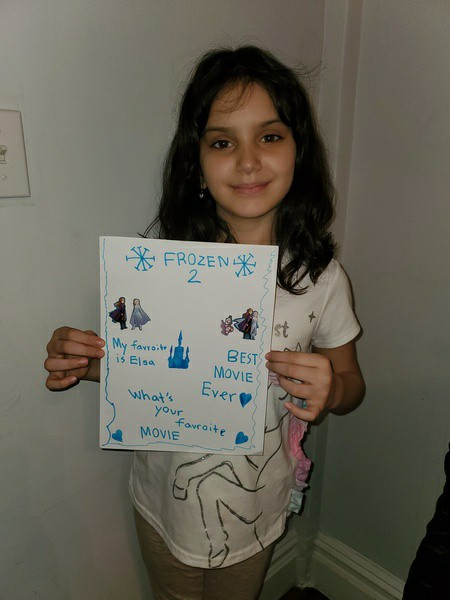 girl holds her picture and captions