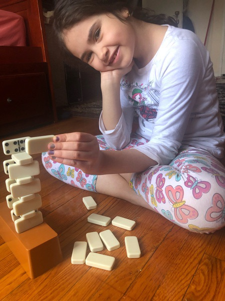 the girl makes the building using dominos