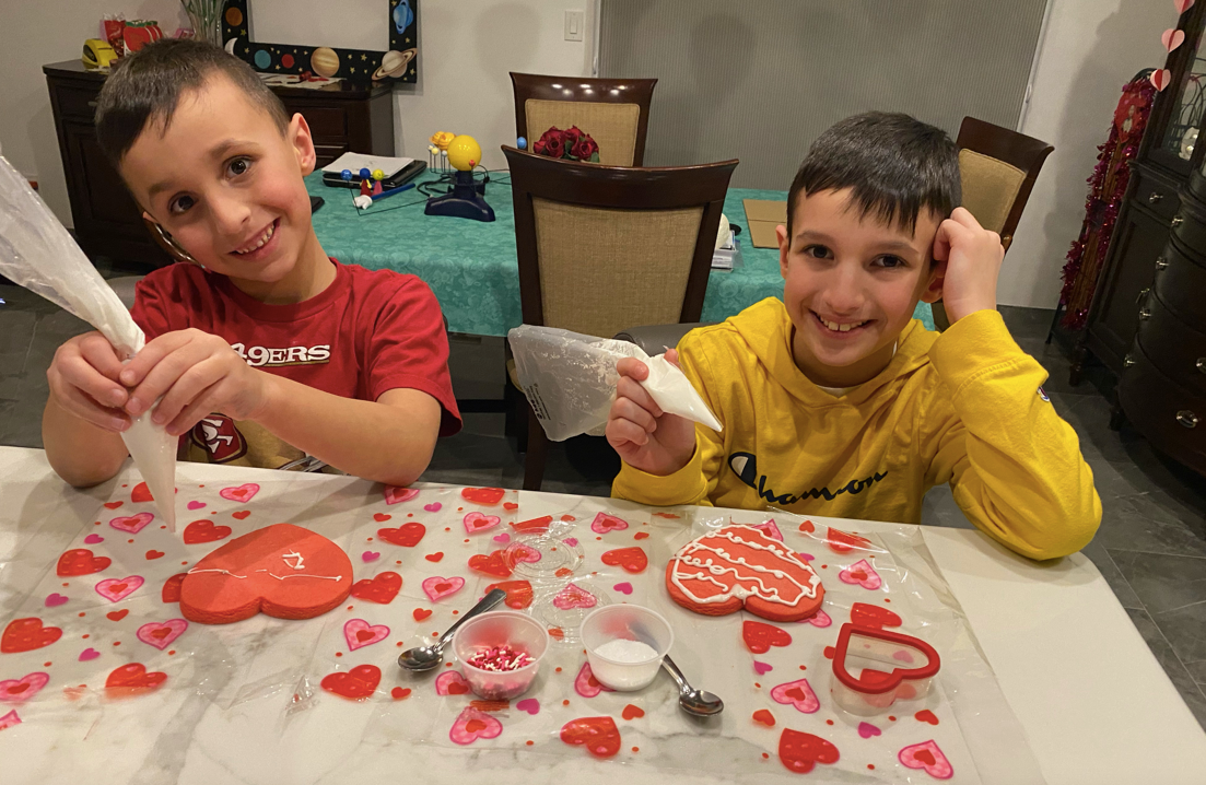 boys giving cute smiles as they decorate cookies