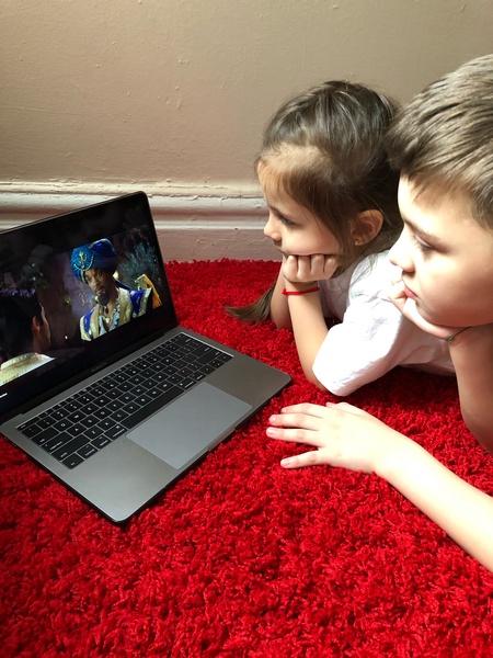 siblings watching movie on laptop