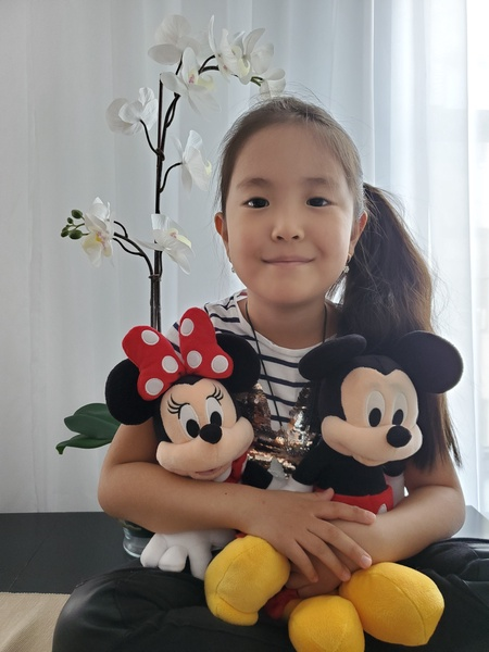 girl holding Mickey Mouse and Minnie Mouse