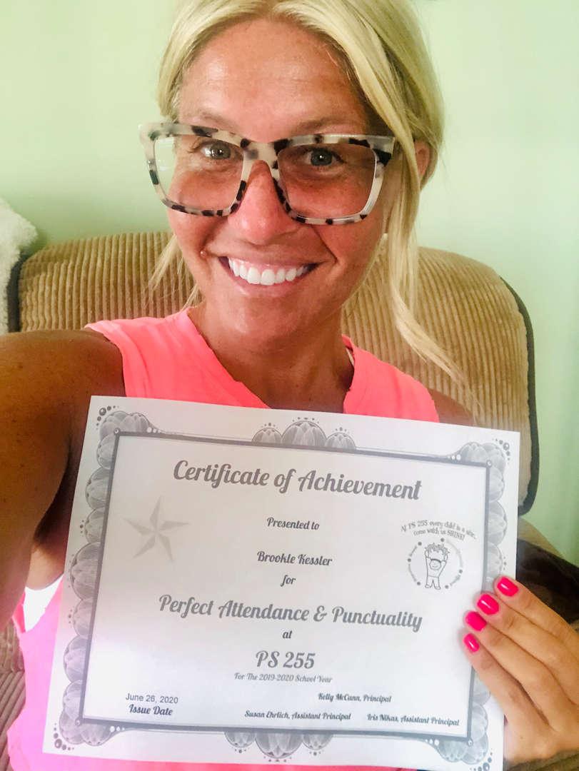 Ms. Kessler holds her certificate smiling