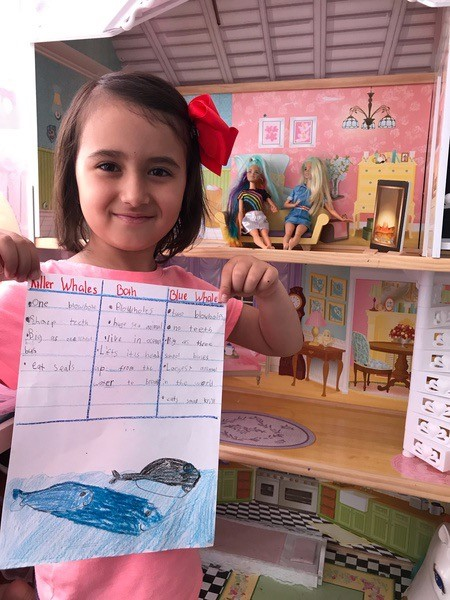 girl smiles as she shows her work