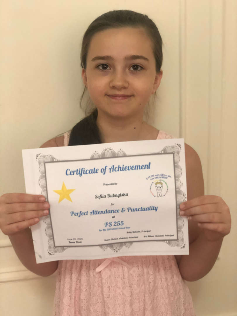 close up of girl holding certificate in front of a white door