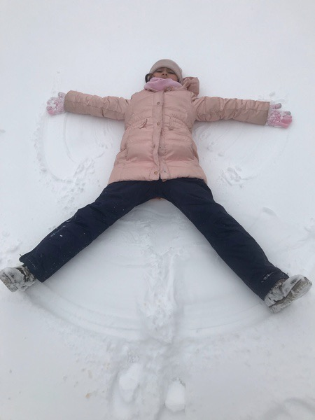 girl playing in the snow with a pink coat and black pants