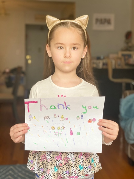 child holds a thank you sign looking serious