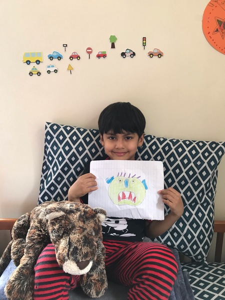 child holds his picture with a blanket on his lap