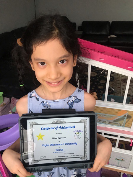 girl standing in front of a doll house holds her certificate