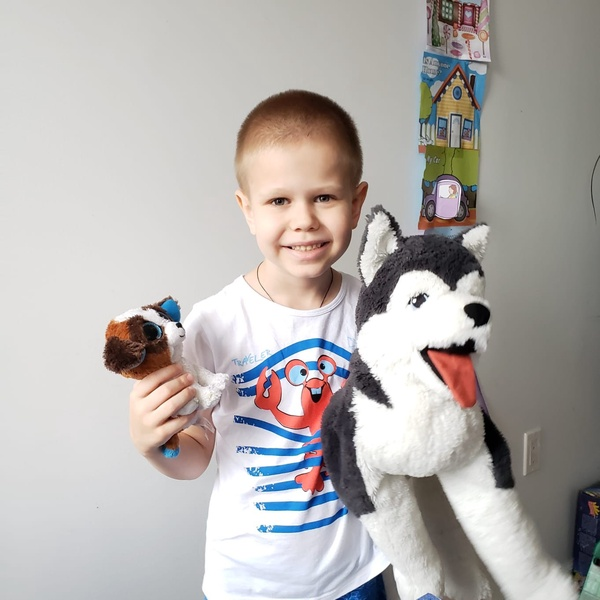 child standing holding two stuffed animals