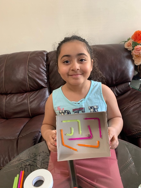 child smiles as she holds her maze