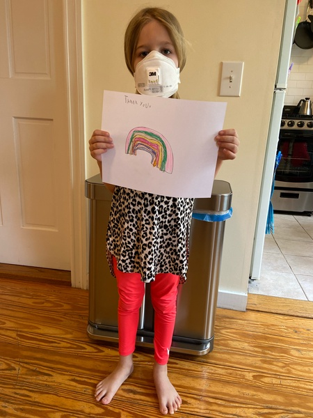 girl in red pants holds her rainbow