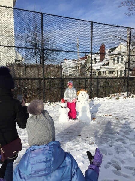 girl standing with two snowmen