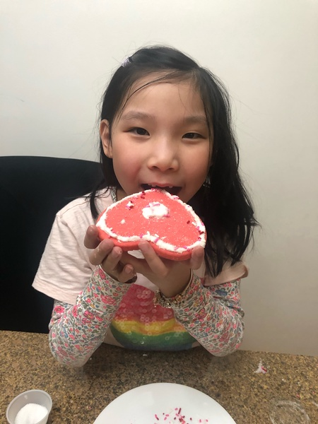 girl about to bite her heart decorated cookie