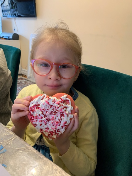 girl wearing glasses showing her decorated cookie