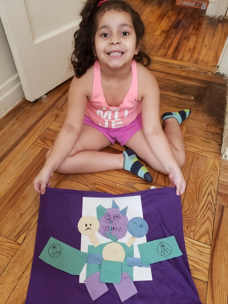 child sitting on the floor holding drawing on a purple frame