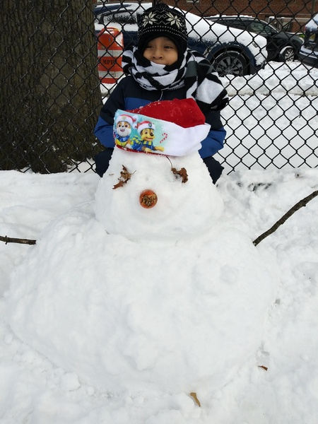 child with a snowman with a holiday hat