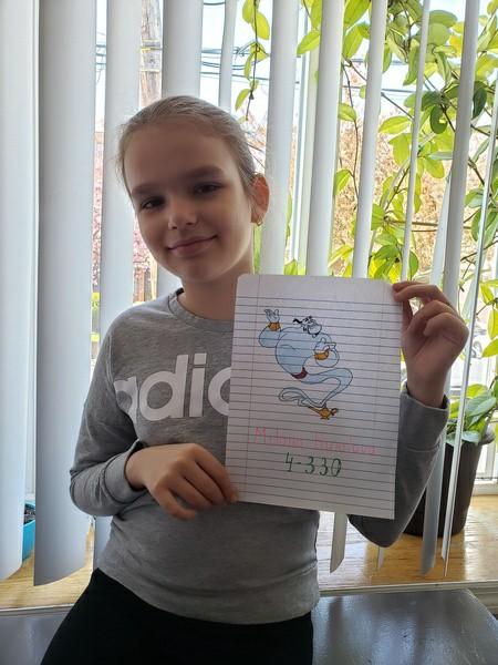 boy smiles holding the genie her drew