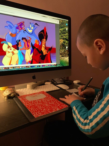 boy works while watching Aladdin