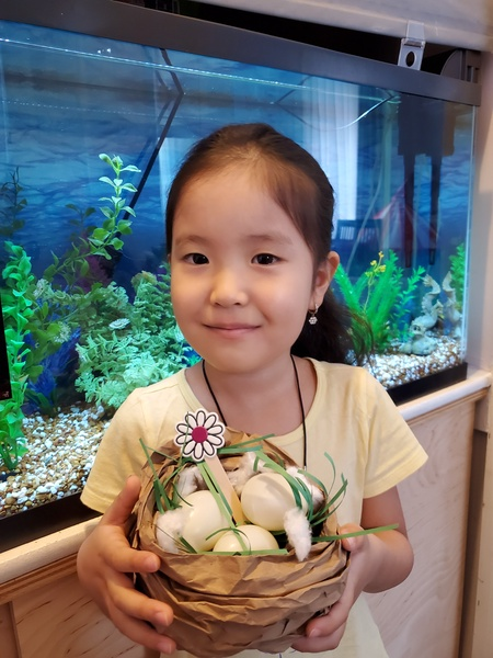 the girls smiles with her creation in front of the fishtanks